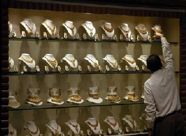 A salesman arranges gold necklaces at a jewellery showroom.