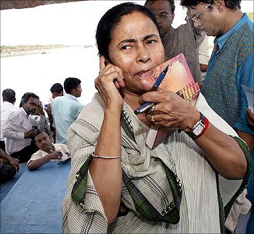 Mamata Banerjee speaks on a mobile phone during her visit to a cyclone-hit site in West Bengal.