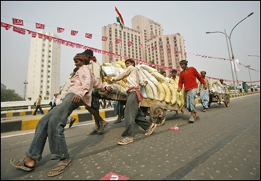 Labourers try to slow down a hand cart loaded with sacks of sand at a flyover in New Delhi.