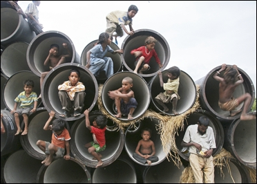 Children play in water pipes at a construction site on the banks of the Yamuna River.