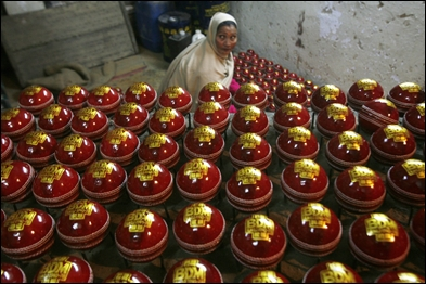 A worker shines cricket balls before packing them at a factory in Meerut.