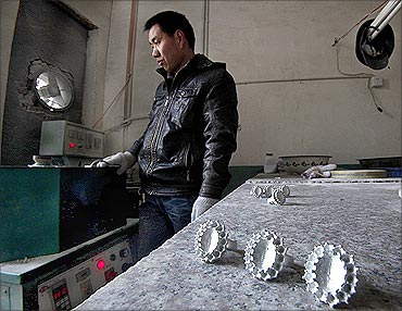 An employee melts metal as he stands next to replicas of the British royal engagement ring.