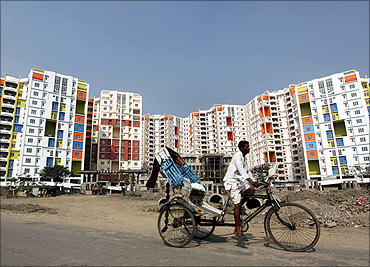 A man rides his cycle rickshaw past newly-constructed residential buildings.