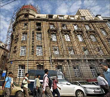 Commuters walk past the headquarters of Central Bank of India in Mumbai.