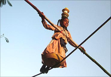 Gita, 9, walks on a rope to earn her living on a street of Bhopal.