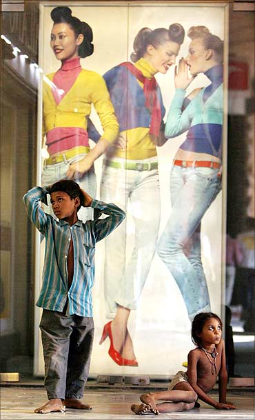 Homeless children are seen in front of a display window of a garment showroom in New Delhi.