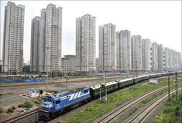 A train runs past newly-built residential buildings in Shenyang, Liaoning province.