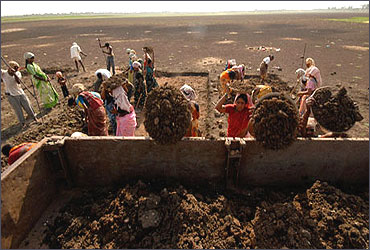 Labourers load a truck as they try to revive a dried lake under the NREGA at Ibrahimpatnam, Hyderabad.