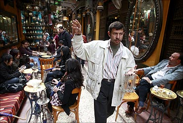 A street vendor selling necklaces passes through a famous shisha bar in the Khan al-Khalili area of Cairo.