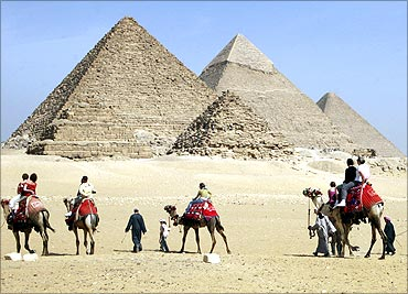 Tourists ride camels at the Pyramids in Cairo.