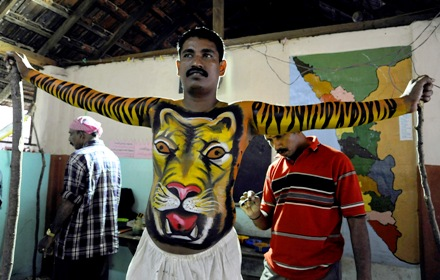 A dancer has his body painted to look like a tiger before he performs during Onam festival in Trichur, Kerala.