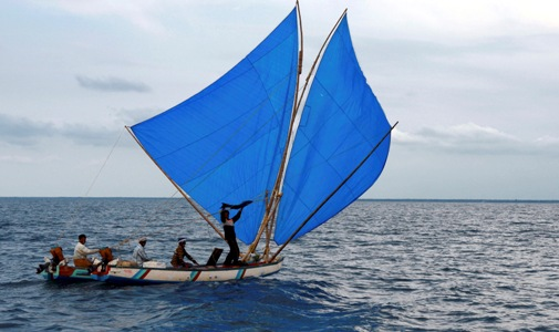 An Indian fisherman shows a fish to the participants of the Volvo Ocean Race in Kochi.
