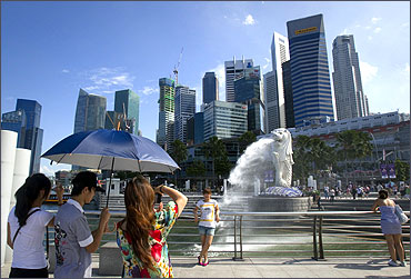 Merlion, the mascot of Singapore, and the financial district skyline.