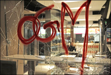 A tag OGM referring to genetically modified plants is seen sprayed on a broken window of a McDonald.