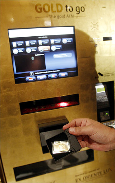 A man holds a gold bar after the unveiling of the first gold-plated ATM at a Madrid's luxury hotel.