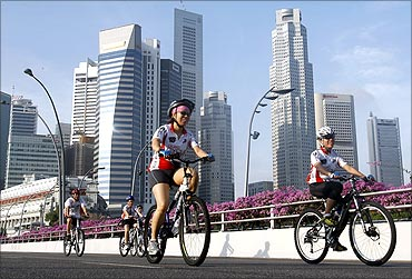Participants cycle past the financial district skyline during the OCBC Cycle Singapore event.