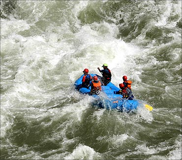 Tourists enjoy white water rafting in river Chenab.