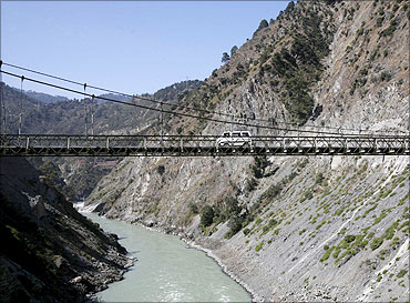 A vehicle moves across a bridge on river Chenab.