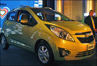Karl Slym, president and managing director of General Motors India sits next to a Chevrolet Beat.