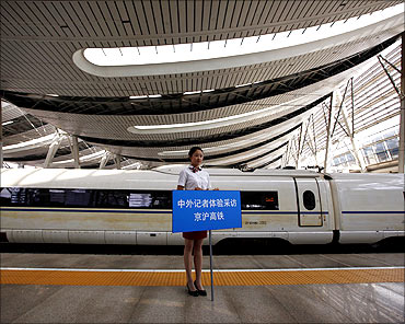 A platform guide holds a sign beside a new high-speed train at Beijing South Railway Station.