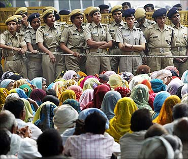 Police stand guard as farmers listen to a speaker during a protest in New Delhi.