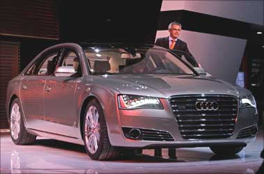 A staff member stands next to a new Audi A8 L W12 Quattro car during its world premiere ceremony at the Beijing Auto Show in Beijing April 23, 2010.