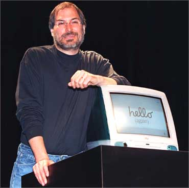 Jobs stands by iMac computer as he addresses the Apple Expo in Paris on Sept 17, 1998.