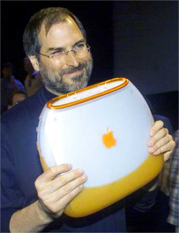 Jobs poses with Apple's iBook portable computer at the MacWorld computer trade show in New York on July 21, 1999.