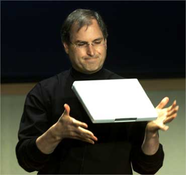 Jobs throws the lightweight Apple iBook notebook computer up in the air on May 1, 2001.