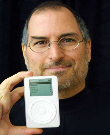 Jobs holds up the MP3 music player at an exibition on October 23, 2001.
