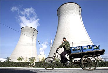 A worker drives his tricycle in front of a power plant on the outskirts of Beijing.