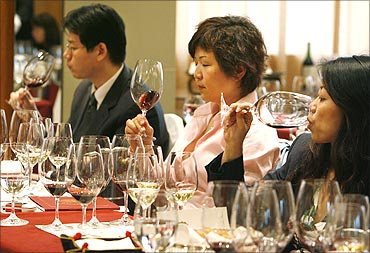 Wine lovers try red wine during a Chateau Haut Brion wine-tasting event in Beijing.