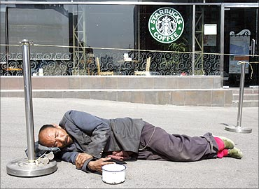 A beggar sleeps in front of a coffee shop in Beijing.