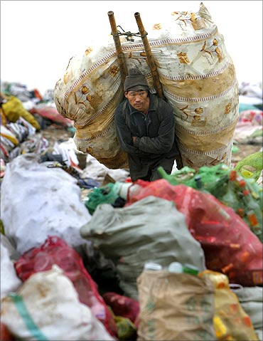 A man carries a package on his back at a garbage dump site in Nanjing.