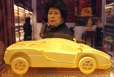 A woman looks at a gold car on display at China International Jewellery Fair in Beijing.