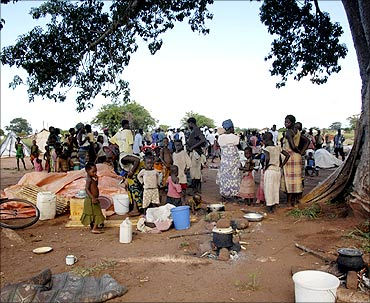 Families displaced by the floods wait under a tree before registration
