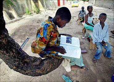 A boy reads a school book at a village just outside Mali's capital Bamako