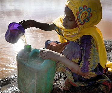 A child collects water from a pond used by animals