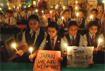 Students hold candles as they pray for Japan's earthquake victims inside their school in Ahmedabad.