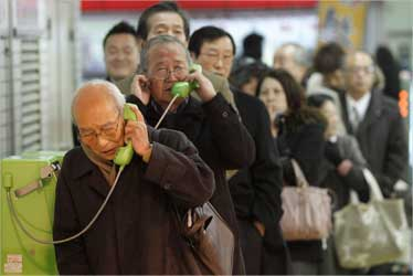 Stranded people stand in a line to use public telephones at a train station.
