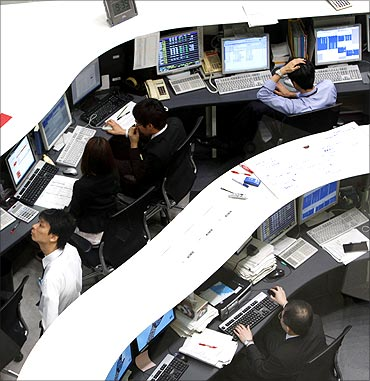 Employees of the Tokyo Stock Exchange (TSE) work at the bourse in Tokyo.