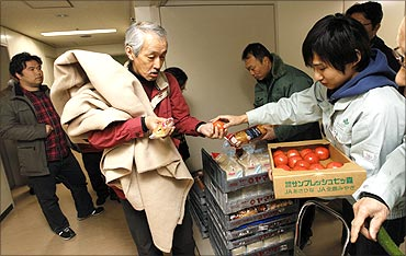An evacuee receives food from government officers in an aisle at an evacuation centre in Sendai.