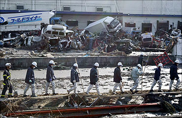 Rescue workers walk in a line to look for survivors at a devastated factory area.