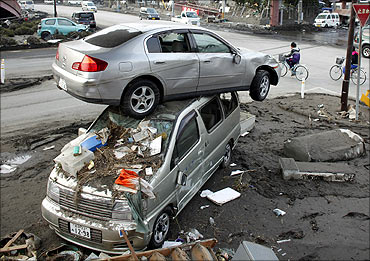 A car sits atop another in an area affected by an earthquake and tsunami in Miyako.