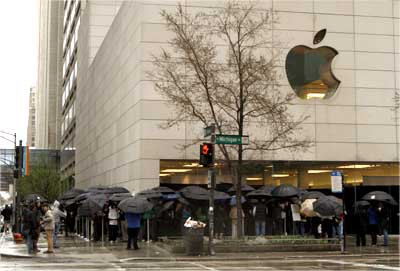 Hundreds of people stand in line in a steady rain to purchase the iPad.