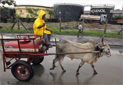 A worker transporting fuel in a bullock cart travels past Indian Oil Corporation's depot in Mumbai.