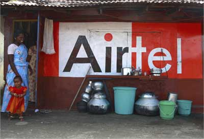 Women and a child stand next to a shop painted with an advertisement of Bharti Airtel in Kochi.