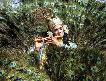 An artist dressed as Lord Krishna performs during a media preview of the 25th Surajkund Crafts Fair.