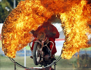 An Indian army soldier performs a motorcycle stunt through a ring of fire in Ahmedabad.