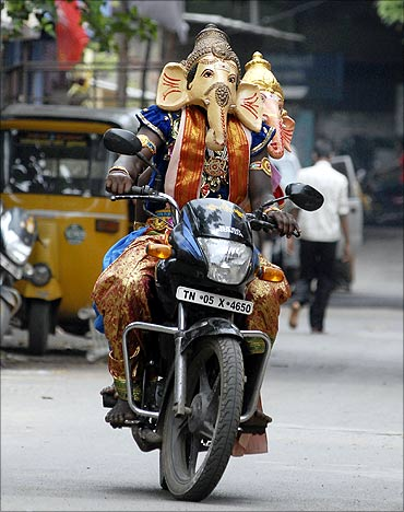 A man dressed as a Hindu god Ganesh, the deity of prosperity, rides a motorcycle.